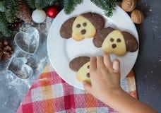以一条狗的形式曲奇饼在圣诞节桌上 新年的标志2018年 孩子采取曲奇饼 免版税库存图片