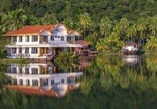 以一艘船的形式热带房子在海旁边在有绿色棕榈树的密林 在海岛上的豪华海滩胜地 免版税库存图片