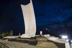 以一艘船的形式纪念碑有在伏尔加河堤防的一个白色风帆的在翼果俄罗斯的晚上 免版税库存图片