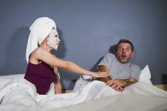 以与妻子的男人和妇女滑稽的生活方式画象奇怪的已婚夫妇为特色要求顶头毛巾和构成的面膜的se 免版税库存图片