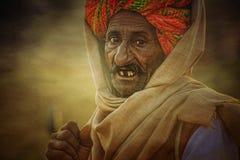 以他的骆驼为背景的老Rajasthani人 免版税库存图片