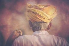 以他的骆驼为背景的老Rajasthani人 库存照片