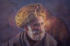 以他的骆驼为背景的老Rajasthani人 免版税库存照片