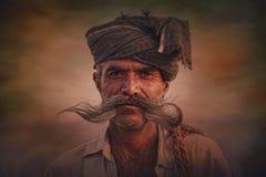 以他的骆驼为背景的老Rajasthani人 免版税图库摄影