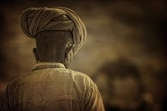 以他的骆驼为背景的老Rajasthani人 库存图片