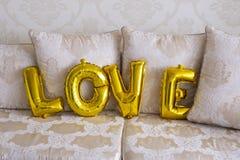 以信件的形式可膨胀的气球 金黄信件爱 免版税库存照片