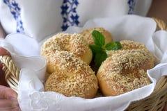 以八的形式与坚果面包屑,妇女拿着一个篮子用传统罗马尼亚和摩尔达维亚甜小圆面包 库存图片