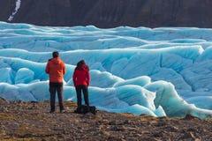 以前站立Skaftafell冰川瓦特纳冰川国家公园美好的平衡的风景的年轻人和妇女在冰岛 免版税图库摄影