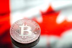 以加拿大旗子为背景的硬币Bitcoin,概念  免版税图库摄影