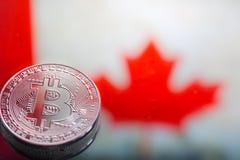以加拿大旗子为背景的硬币Bitcoin,真正金钱,特写镜头的概念 背景黑色概念概念性费用房主房子图象挣的货币表示 库存图片
