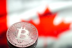 以加拿大旗子为背景的硬币Bitcoin,真正金钱,特写镜头的概念 背景黑色概念概念性费用房主房子图象挣的货币表示 免版税库存照片