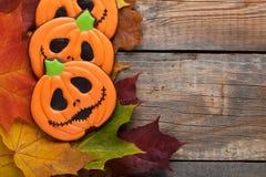 以南瓜的形式自创姜饼曲奇饼为万圣夜 秋天在老木背景的槭树叶子 与c的顶视图 库存图片