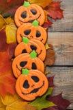 以南瓜的形式自创姜饼曲奇饼为万圣夜 秋天在老木背景的槭树叶子 顶视图 免版税库存图片