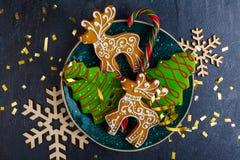 以圣诞树和鹿的形式圣诞节姜饼,在桌旁边是木雪花 在视图之上 免版税库存照片