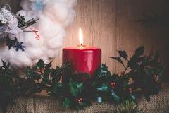 以圣诞节花圈为背景的灼烧的蜡烛和霍莉分支由棉绒制成 免版税图库摄影