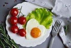 以在一块白色板材服务的心脏的形式鲜美煎蛋 库存照片
