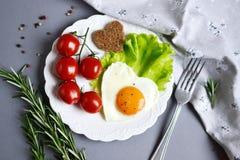 以在一块白色板材服务的心脏的形式鲜美煎蛋 免版税图库摄影