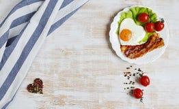 以在一块白色板材服务的心脏的形式鲜美煎蛋 免版税库存照片