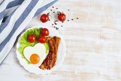 以在一块白色板材服务的心脏的形式鲜美煎蛋 免版税库存图片