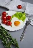 以在一块白色板材服务的心脏的形式鲜美煎蛋 库存图片