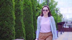 以在拐杖的伤害步行沿着向下街道的美丽的时髦的正面年轻女人晴朗 股票视频