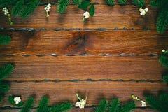 以在木棕色背景的一个框架的形式圣诞节冷杉分支 中看不中用的物品蓝色圣诞节构成玻璃 免版税库存照片