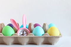 以在纸包装的一只兔子的形式上色复活节彩蛋和桃红色手表 库存图片
