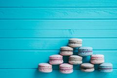 以在绿松石木背景, Macaron或蛋白杏仁饼干说谎,顶视图,拷贝空间的一座金字塔的形式 免版税库存图片