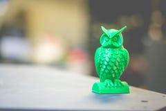 以在3d打印机黑暗背景创造的一头小猫头鹰的形式绿色形式 免版税图库摄影