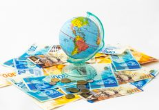 以地球的形式被做的钱箱,与金钱槽孔的行星地球在上面在堆站立d以色列钞票  免版税库存图片
