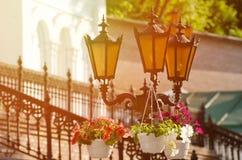 以墙壁和伪造的楼梯为背景的三橙色街灯 免版税库存图片