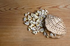 以壳的形式,在木桌背景,焦糖的焦糖玉米花调味了在一个柳条筐的玉米花 图库摄影