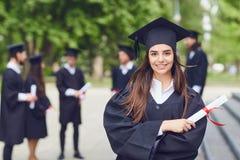 以大学毕业生为背景的一个年轻女性毕业生 免版税图库摄影