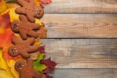 以姜饼人吸血鬼的形式自创饼干为万圣夜 秋天在老木背景的槭树叶子 顶视图机智 库存照片