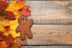 以姜饼人吸血鬼的形式自创饼干为万圣夜 秋天在老木背景的槭树叶子 顶视图机智 库存图片