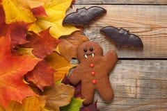 以姜饼人吸血鬼的形式自创饼干为万圣夜 秋天在老木背景的槭树叶子 顶视图 免版税图库摄影