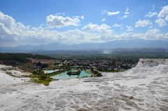 以山、城市和夏天天空蔚蓝为背景的雪白石灰华与云彩在棉花堡,土耳其 库存图片