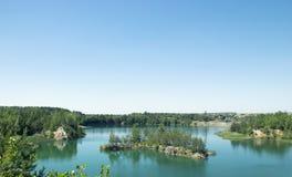 以弧的形式一个海岛在岩石附近的一个大湖中间 免版税库存图片