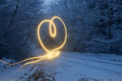 以心脏的形式光线影响 冬天森林在晚上 免版税库存照片