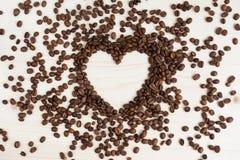 以心脏的形式咖啡豆在木背景 免版税库存照片