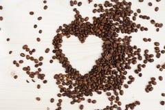 以心脏的形式咖啡豆在白色背景 免版税库存图片