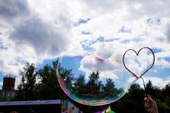 以心脏的形式大肥皂泡在天空 库存照片