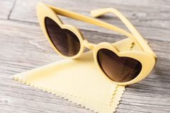 以心脏的形式太阳镜和抹的玻璃一块餐巾在轻的木背景 免版税库存图片