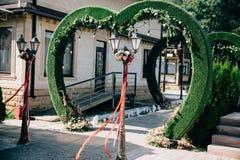 以心脏的形式婚礼曲拱,用在草坪的花装饰的法坛 免版税库存图片