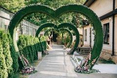 以心脏的形式婚礼曲拱,用在草坪的花装饰的法坛 库存照片