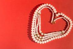 以心脏的形式安置的珍珠 免版税库存照片