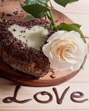 以心脏的形式巧克力杯形蛋糕,装饰用一朵白色玫瑰的花,在木背景 免版税库存照片
