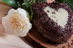 以心脏的形式巧克力杯形蛋糕,装饰用一朵白色玫瑰的花,在木背景 免版税库存图片