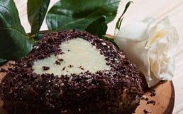 以心脏的形式巧克力杯形蛋糕,装饰用一朵白色玫瑰的花,在木背景 库存照片