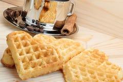 以心脏的形式曲奇饼在与一杯咖啡的木背景、桂香和茴香 免版税库存照片